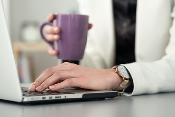Close up view of female student at workplace holding cup of tea