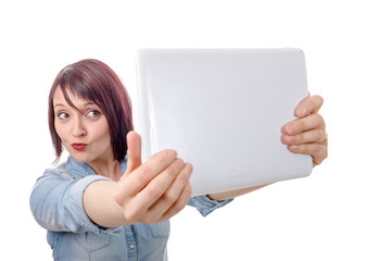 Attractive young  woman taking selfie with tablet in a studio
