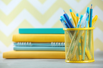 Stationery in metal holder on books background
