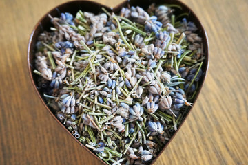 Heart of dried lavender in paper box on wood