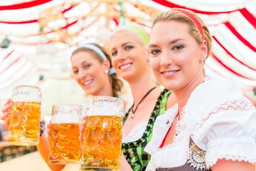Freundinnen trinken zusammen Bier im Bayrischen Dirndl auf Volksfest