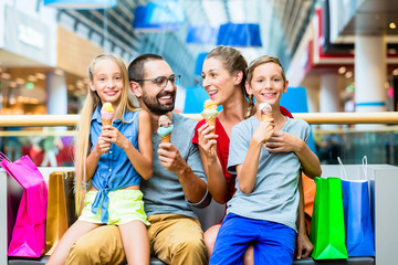 Family eating ice cream in shopping mall with bags