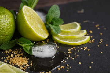Fresh lime, mint and ice cubes. Dark background