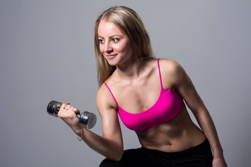 Athletic young woman doing a fitness workout with dumbbells on gray studio background