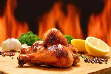 Roast chicken legs and various vegetables on a chopping wood