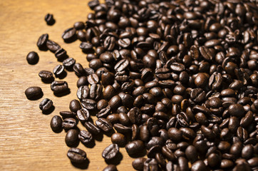 Coffee beans scattered across a wooden table.