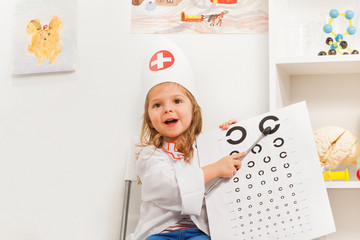 Girl playing doctor with oculist sign and pointer