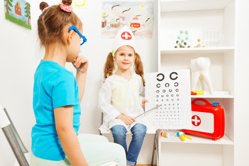 Little girls playing a doctor ophthalmologist