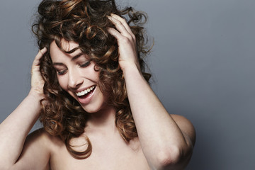 Young woman touching curls, smiling