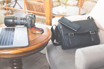 Laptop computer and dslr camera at cafe