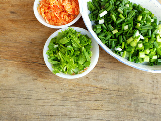 chopped green onions and coriander with dried shirmp on the wooden background