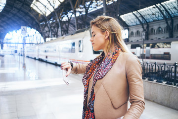 young beautiful modern business woman looking at her watch while waiting for the train at the railway station