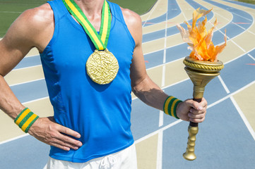 Gold medal athlete holding ceremonial sport torch with inspirational flame in front of running track