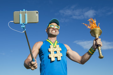 Gold medal athlete smiling for a selfie with a sport torch against bright blue sky