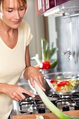 femme dans une cuisine coupant des poireaux