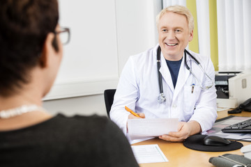Happy Doctor Looking At Female Patient At Desk