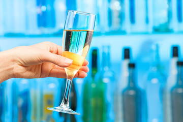 Woman hand toasting champagne in crystal glass