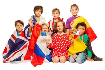 Seven kids with flags wrapped in different banners