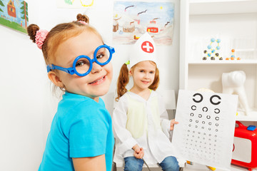 Girl in blue toy glasses at ophthalmologist room