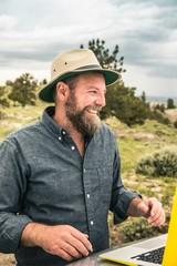 Happy man on road trip using laptop on car bonnet, Cody, Wyoming, USA