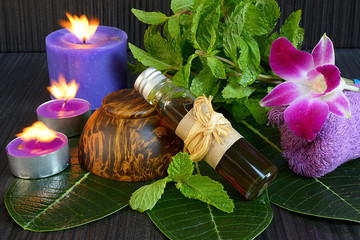 Essential aroma oil with peppermint on wooden background.