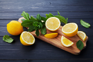 Lemon and mint leaves served on wooden kitchen board on black rustic table, ingredient for summer cocktails and lemonade