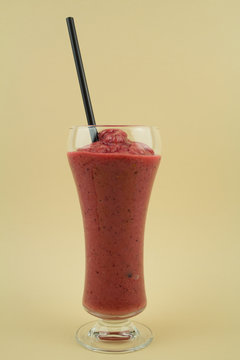 Fruitshake in a Glass with a Straw.