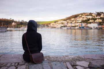 Young woman sitting by water in small town