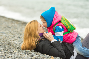 Five-year girl sitting astride a mother who is lying on the pebbly shore of the sea, and kisses her on the nose