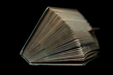 Stara książka z lekko rozchylonymi stronicami na ciemnym tle w naturalnym oświetleniu. Ujęcie od góry-przodu.Widoczna wystająca zakładka