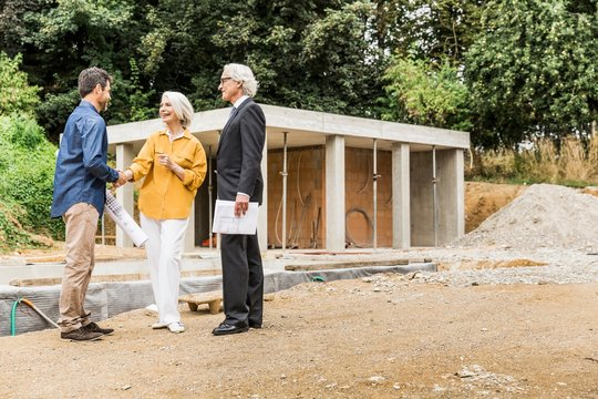 Couple on construction site shaking hands with architect smiling