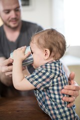 Father helping baby boy to drink from mug