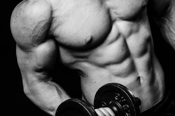 Close up of muscular bodybuilder guy doing exercises with weights dumbbell over isolated black background. Black and white
