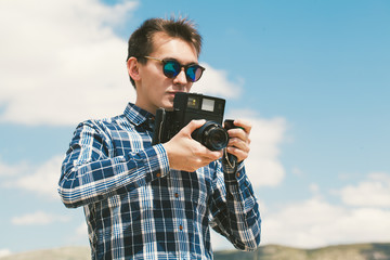 Man taking a picture with an old vintage camera with a blue sky background.