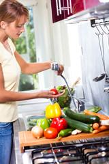 femme qui rince des légumes dans une cuisine
