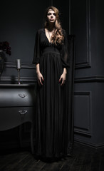 Sexy young woman in black dress standing on background of vintage dark interior