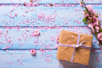 Wrapped box with presentand sakura pink flowers on blue wooden p