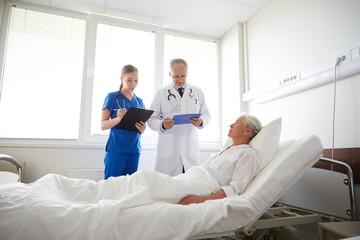doctor and nurse visiting senior woman at hospital