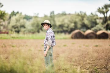 Teenage boy standing looking over his shoulder in ploughed field