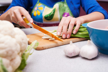 woman cuts green onions