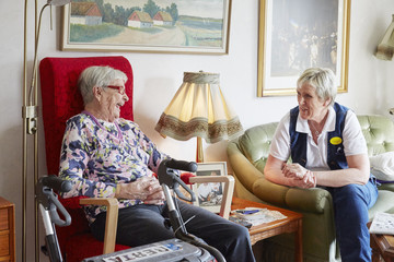 Senior woman talking with nurse in care home