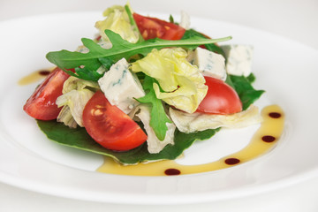 Fresh salad with spinach, cherry tomatoes, arugula and blue cheese. Close up image.