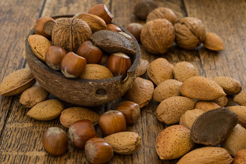 various mixed nuts on wooden table background