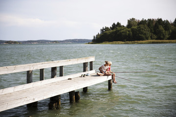 Siblings fishing while sitting on dock