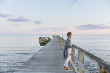 Woman on pier looking at sea