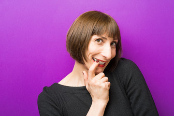 woman points a finger at the tooth