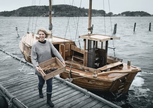 Smiling woman carrying lobsters, boat on background