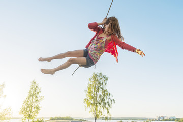 Girl swinging on rope outdoors