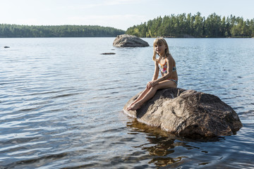 Girl on rock in lake