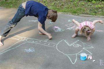 Sibling children playing during sidewalk chalking on asphalt surface